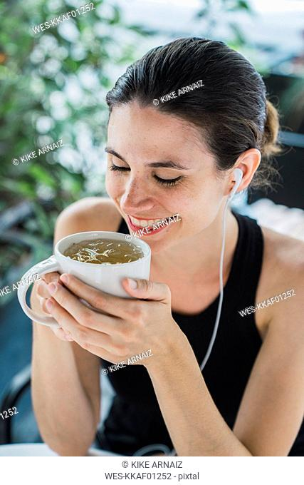 Young businesswoman sitting in coffee shop, taking a break, drinking tea