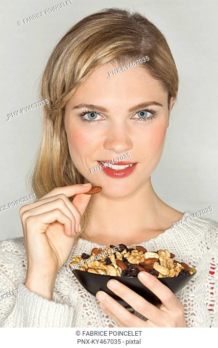 Portrait of a beautiful woman eating dried fruit