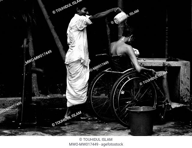 A patient having a bath, at the Half Way Hostel of 'The Centre for the Rehabilitation of the Paralyzed', or CRP, located in Savar