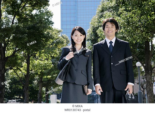 A mid adult businessman and a young businesswoman standing