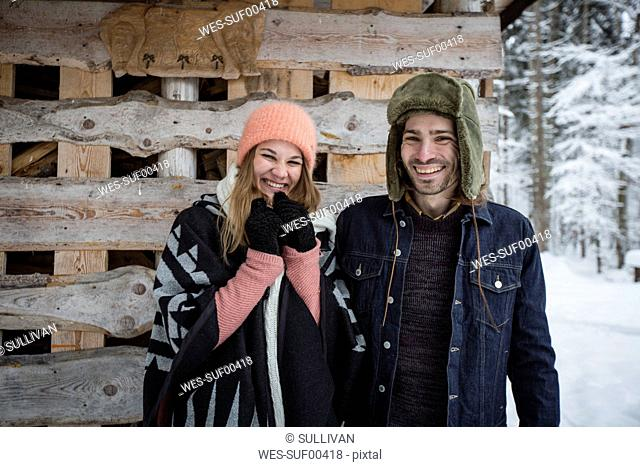 Portrait of happy couple in front of wood pile outdoors in winter