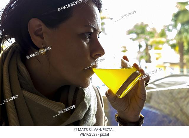 Woman Drinking Orange Juice in Switzerland
