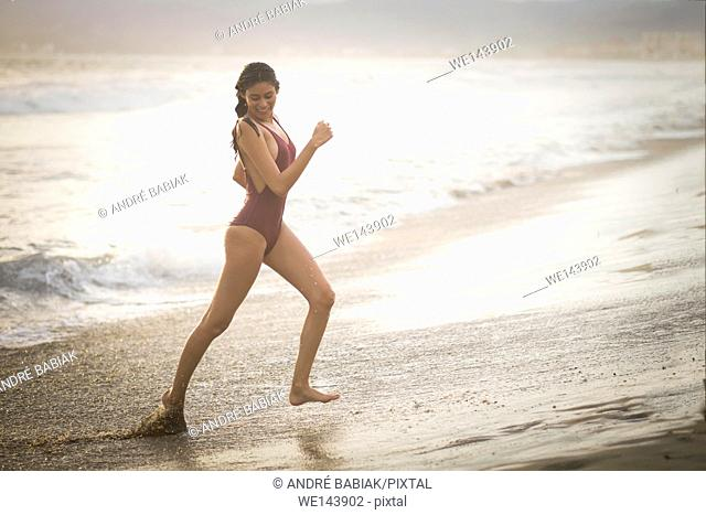 Young attractive woman in swimsuit running at the beach before sunset hour