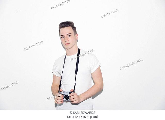 Portrait confident, cool teenage boy holding retro camera