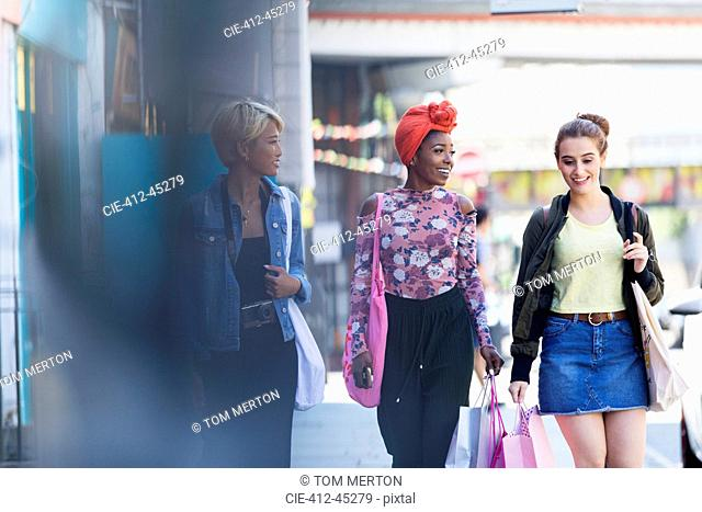 Young women friends walking with shopping bags on urban sidewalk