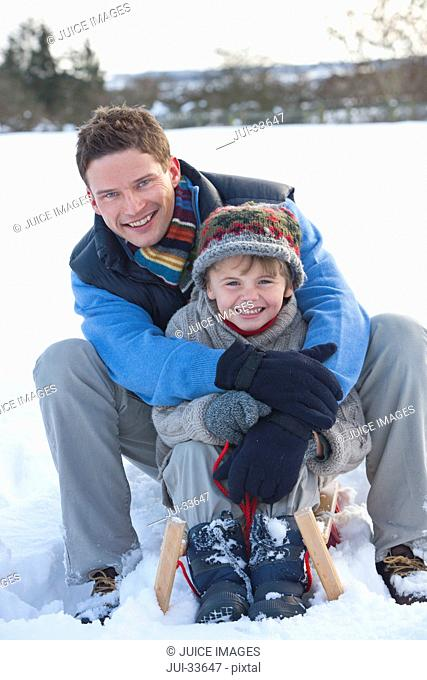 Portrait of smiling father and son sitting on sled and hugging in snow