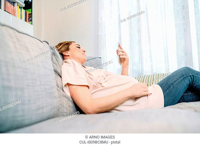 Pregnant woman on sofa looking at smartphone