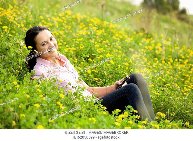 Young woman sitting on a meadow, listening to music