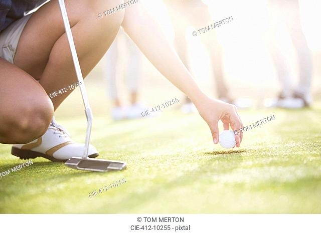 Woman removing golf ball from hole