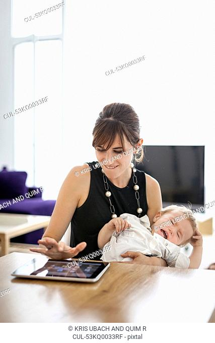 Businesswoman holding crying son