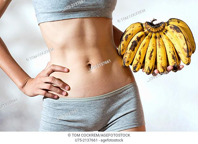 Fit and slim young woman with tight abdomen holding a bunch of bananas