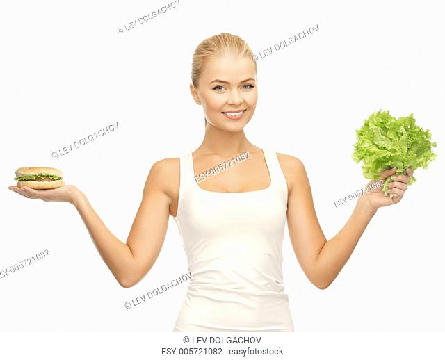picture of sporty woman with green lettuce and hamburger