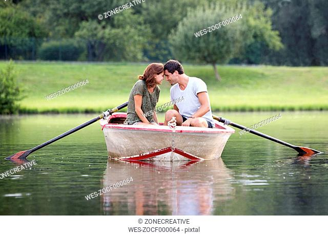 Young couple face to face in a rowing boat on lake