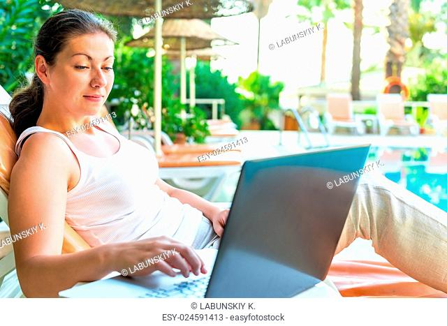 woman in a white T-shirt with a laptop