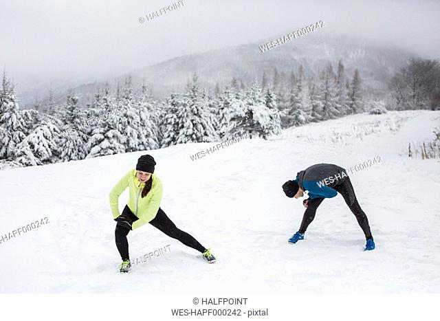 Couple warming up for cross country run in winter