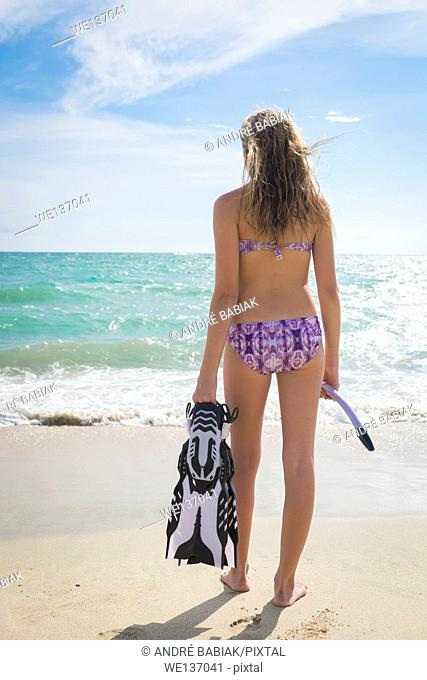 Girl with fins and snorkel is about to enter the sea at a beach. Female teenager, 13 years, Nayarit, Mexico