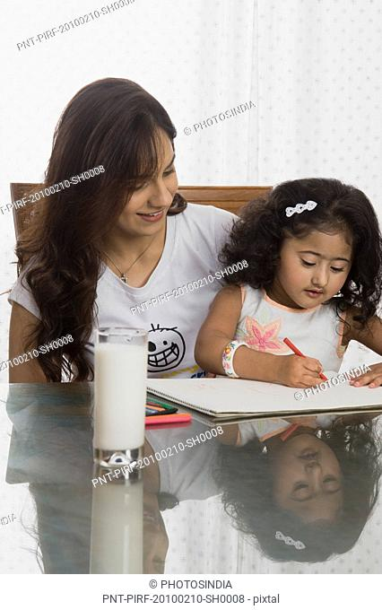 Close-up of a girl drawing with her mother at the dining table