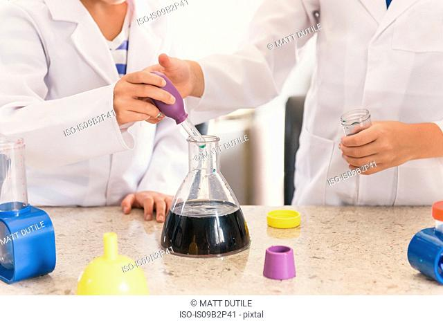 Girls using pipette and conical flask from chemistry set