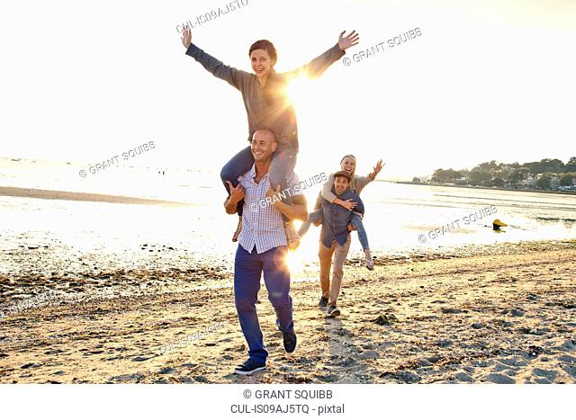 Men giving piggyback ride to women on beach