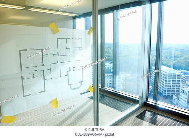 Architectural plans taped to glass wall of empty room
