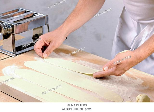 Hands of a man holding rolled out pasta dough for home-made tortelloni