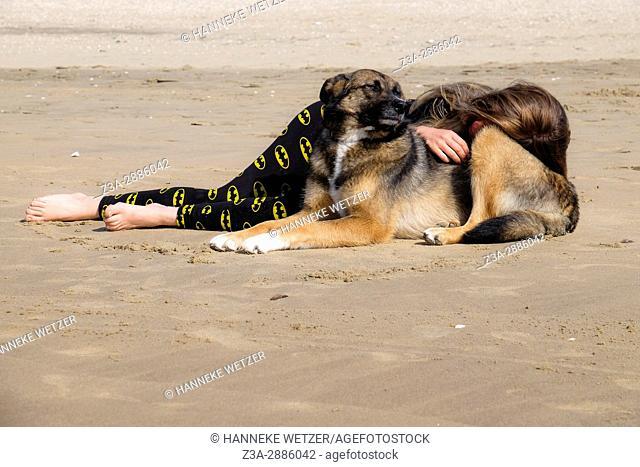 A girl and her dog sleeping at the beach of Scheveningen, The Hague, The Netherlands, Europe