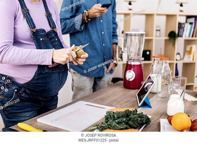 Woman peeling kiwi for preparing fruit smoothie, partial view