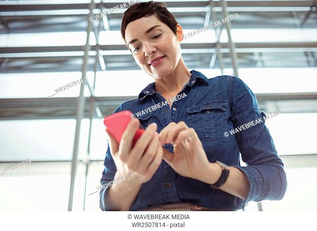 Businesswoman using mobile phone in waiting area