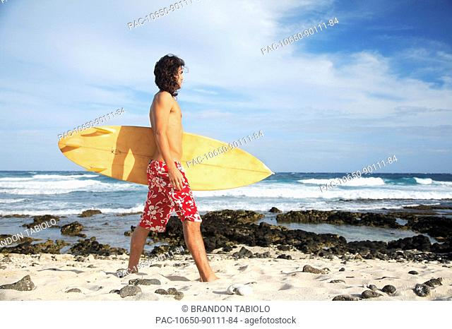 Hawaii, Oahu, young man at the beach with surfboard