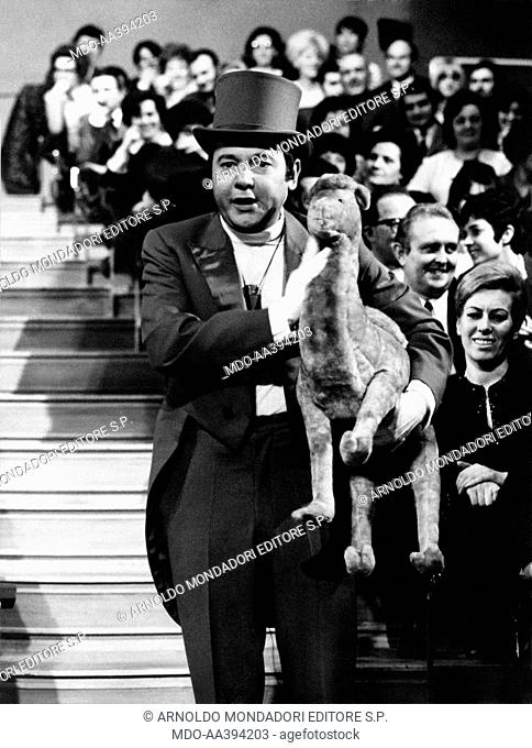 Paolo Villaggio at E' domenica, ma senza impegno. Italian actor, presenter and writer Paolo Villaggio, wearing a top hat and holding a fluffy camel in his hands