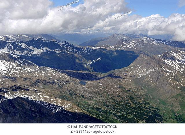 aerial shot, from a small plane, of San Bernardino pass road , shot on a bright summertime day in Swiss mountains, Switzerland