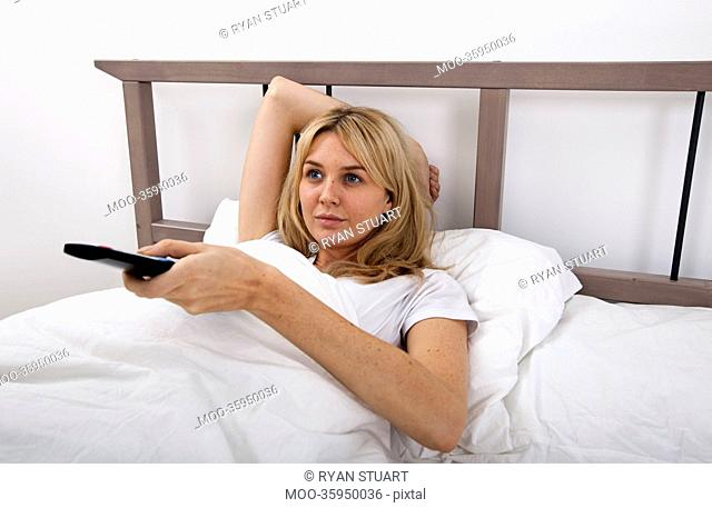 Young woman changing channels with remote control in bed