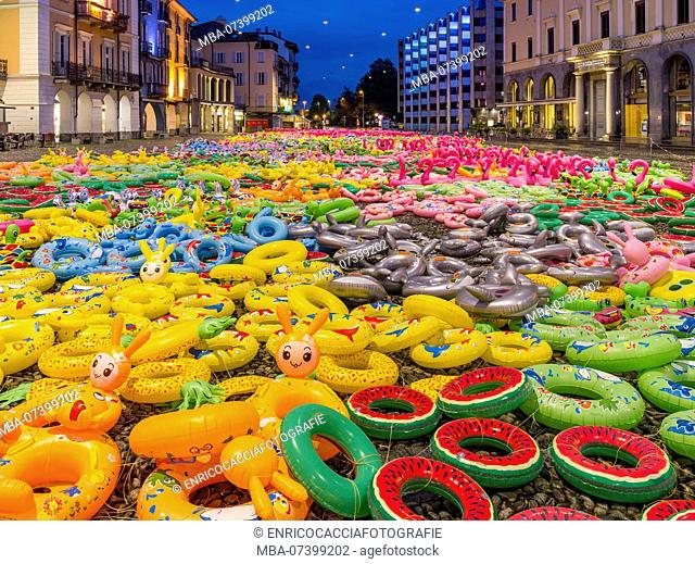 Panorama of the Piazza Grande in Locarno in the evening with art installation made of colorful swimming tyres