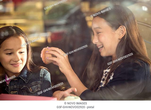 Two Smiling Young Girls Eating Cupcakes in Café Window