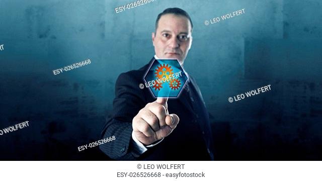 Male entrepreneur is pressing a hexagonal push button displaying three gear wheels. The virtual icon is lighting up. Business concept and technology metaphor...