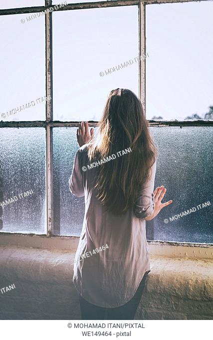 Rear view of a woman waiting by the window