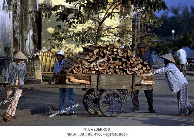 Three mid adult women and a mid adult man pushing a cart full of wood, Vietnam