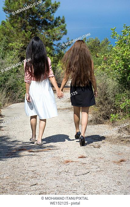 Rear view of two young women walking away together on a countryside road