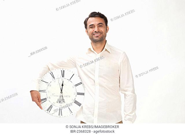 Smiling man holding a clock at eleven fifty-five, almost high noon
