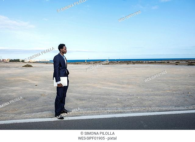 Spain, Tenerife, young businessman with laptop standing on road