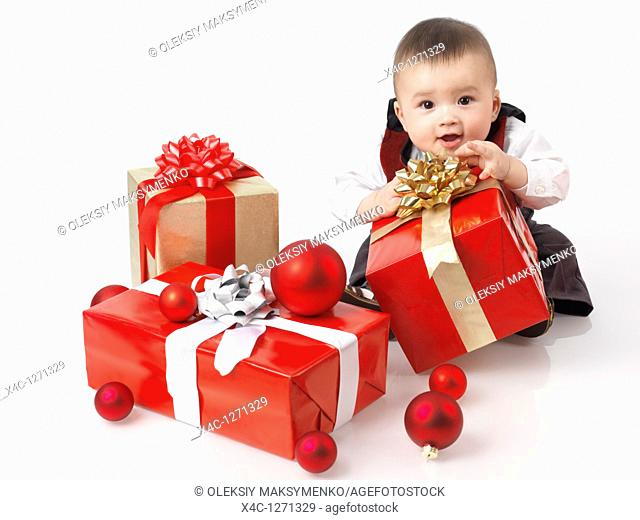 Happy six month old baby boy opening Christmas presents  Isolated on white background