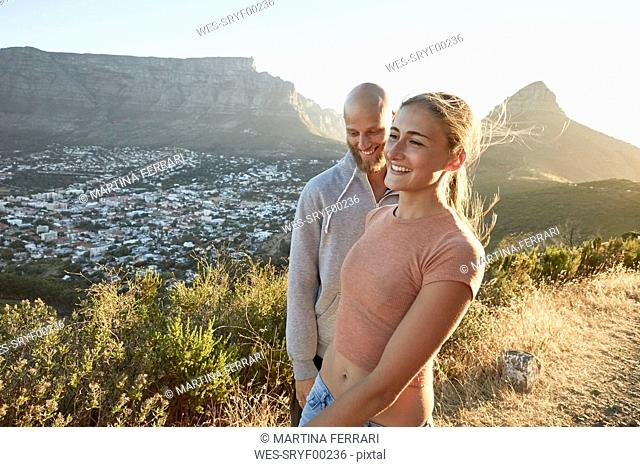 South Africa, Cape Town, happy young couple at roadside at evening twilight