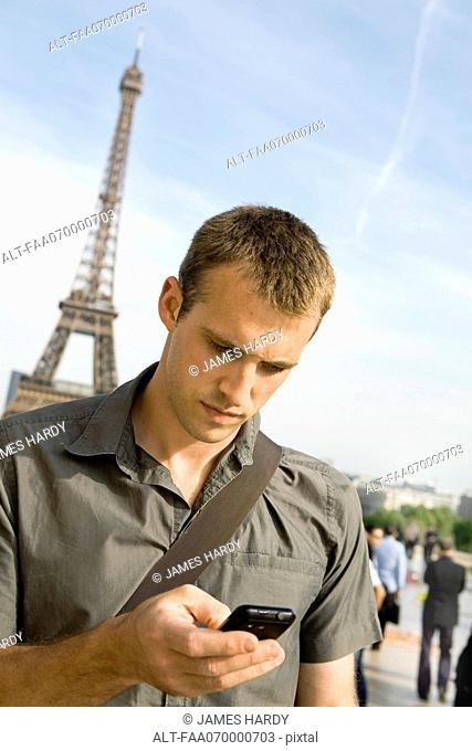 Man text messaging with cell phone, Eiffel Tower in background, Paris, France