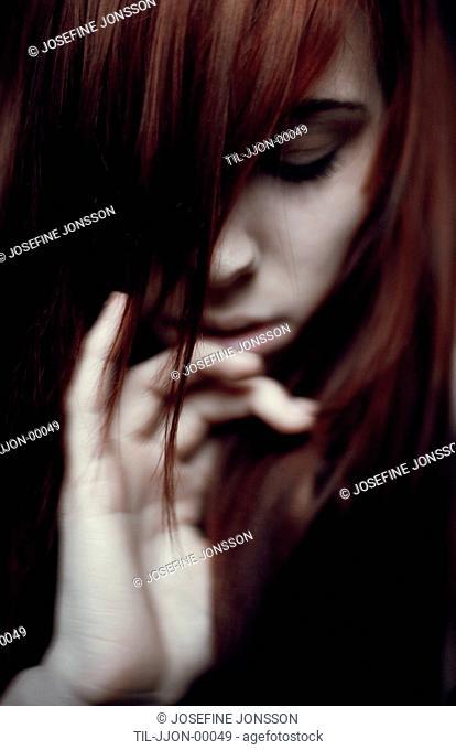 Girl hiding behind hair looking down towards hand under chin