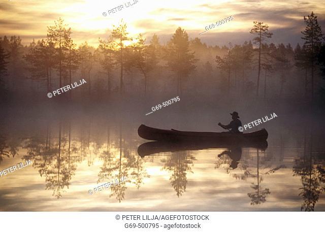 A man paddle a canoe a misty summermorning at a small lake. Byske. Vasterbotten. Sweden