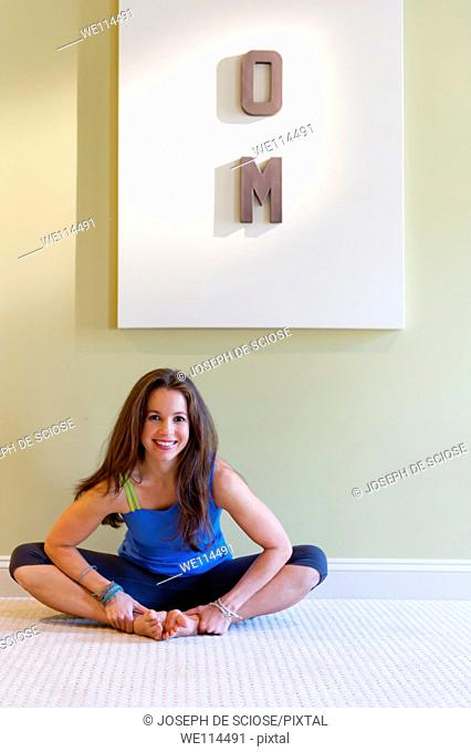 Portrait of a 37 year old brunette woman sitting a on a floor wearing fitness clothing