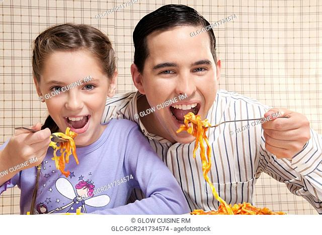 Man and his daughter eating pasta