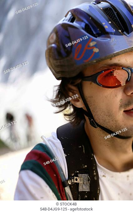Young man with helmet and sunglasses has dirt in his face part of, close-up
