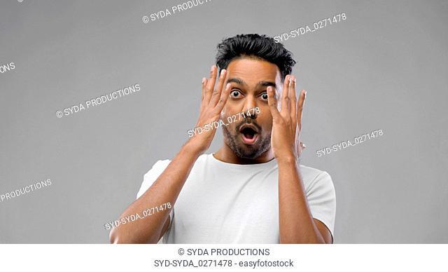 shocked indian man over grey background