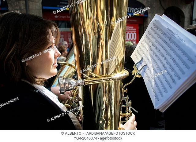 A woman playing the tuba in the marching band during a parade through the streets of Llanes. Asturias.Spain